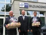 Mit einem kleinen Präsent ehrte Roman Bohle (IHK-Bildungsinstitut, M.) in der IHK-Geschäftsstelle Lippstadt den bundesbesten Bilanzbuchhalter Frank Holtmann-Wibberich (r.) sowie seinen Dozenten Franz-Josef Mertens (l.)
