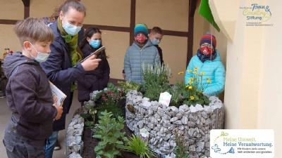 Hort-Leiterin Manuela Schildhauer freut sich mit den Kindern über die NektarTankstelle und das WildbienenHaus
