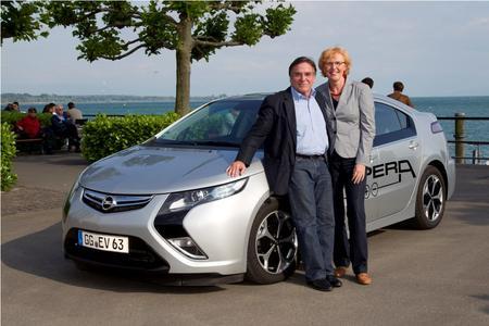 Der Schauspieler Elmar Wepper und seine Frau Anita mit dem Opel Ampera vor der prächtigen Kulisse des Bodensees