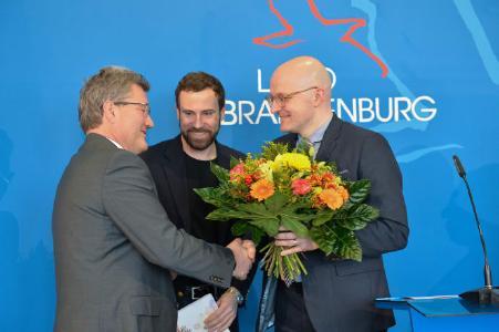 Thomas Kralinski (r.), Chef der Potsdamer Staatskanzlei, beglückwünscht Oculyze-Geschäftsführer Kilian Moser und Team-Berater Prof. Dr. Marcus Frohme (l.) zur Auszeichnung