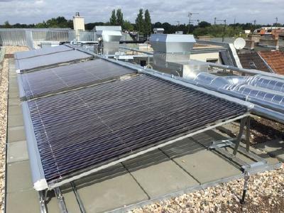 Hochleistungs-Voll-Vakuumröhrenkollektoren auf einem Flachdach mit optimaler Südausrichtung.  Die einzeln um 360° drehbaren Röhren lassen sich zusätzlich ausrichten.
