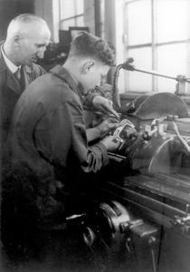 Voll konzentriert: Ein Opel-Lehrling in den 1940er Jahren an der Drehbank. Der Lehrmeister schaut genau zu