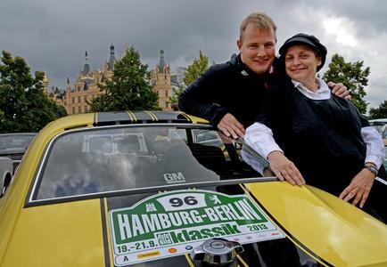 Vor dem Schloss in Schwerin: Schauspielerin Katharina Thalbach und Bob-Olympiasieger André Lange bei der Oldtimer-Rallye Hamburg-Berlin-Klassik 2013 © GM Company