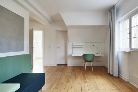 Apartment 2: Der Farbklang dreier Grüntöne in Kombination mit einer grauen, lebendig strukturierten Fläche bildet einen ausgleichenden Kontrast zum warmtonigen Holzboden (Foto: Caparol Farben Lacke Bautenschutz/Blitzwerk und Fotograf Thomas Ott)